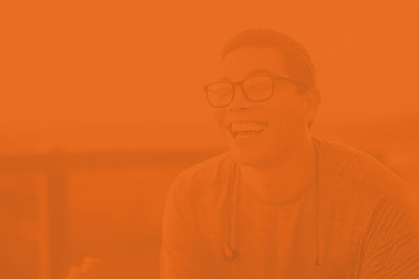Orange overlay of young man with glasses laughing